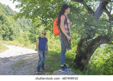 Tourists hitching a ride. Active hikers. Travelers travel on the road in mountains go trekking together. Trekking together