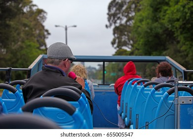 Tourists and a Host on a Hop On Hop Off Open Top Bus