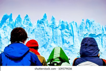 Tourists looking at gigantic icebergs from a ship