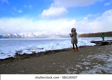 Tourists looking at Lake Kussharo swan closed by ice