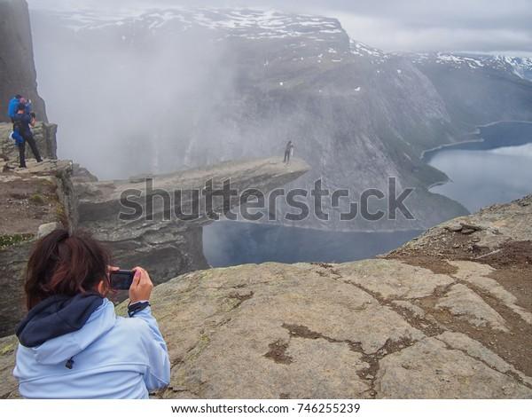 Tourists make dangerous photos at Trolltunga (Norway)