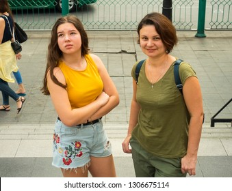 Tourists. Mom and her teenager daughter on the street of an unfamiliar city in summer