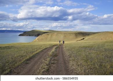 tourists are on the broad road, amid vistas, Lake Baikal, Olkhon Island, Khuzhir town
