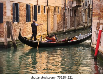 Tourists on a characteristic gondola on a canal in Venice, Italy.