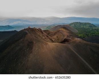 Tourists on edge of Monti De Fiore on volcanic Mount Etna