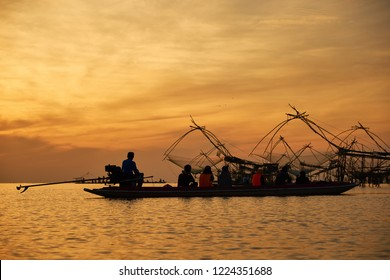 tourists on long tail boat to see sunrise and the large fisherman's tools at Thale noi, Phatthalung, Thailand. silhouette.