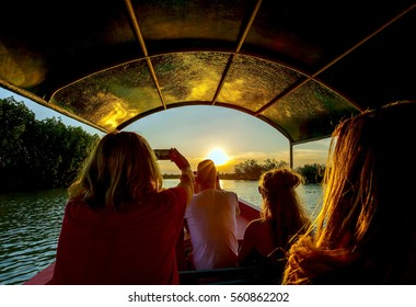 Tourists on long tailed boating tour in mangrove canal during sunset, traveling concept