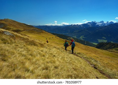 Tourists on the mountain way with Hohe Tauern on backround, Austria