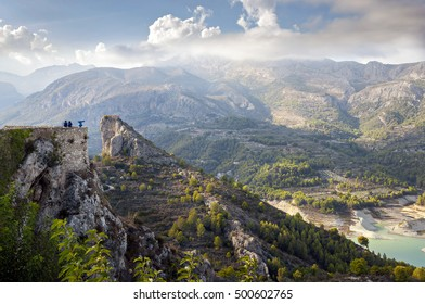 Tourists on the observation deck over the lake neautiful in Guadalest, Spain