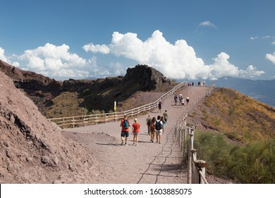 Tourists on the path leading along crater of the Mount Vesuvius, famous Italian volcano near Naples City.