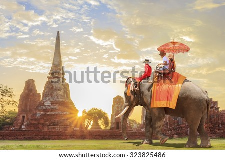Tourists on an ride elephant tour of the ancient city in sunrise background