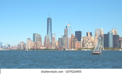Tourists on romantic sailing tour journey down the East River and Hudson River in famous New York City Harbor overlooking Lower Manhattan. People on adventurous yacht cruise on amazing sunny day
