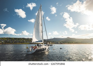 Tourists on the sailing yacht. Northern Ireland. Breathtaking marine scenery. The lone boat on the water surface. Irish shoreline on the horizon. Sunset blue cloudy sky. Beauty of Irish nature.