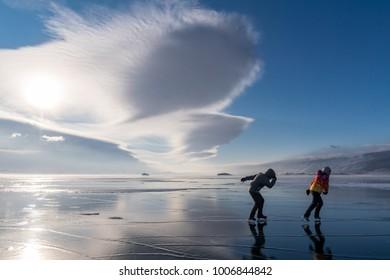 Tourists on skates go to meet the wind on Lake Baikal
