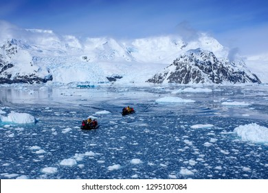 Tourists on zodiacs skimming along the water on their way to the Antarctica continent