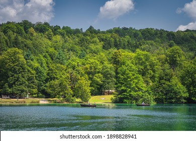 Tourists paddling in two paddleboats on emerald green lake in Plitvice Lakes National Park UNESCO World Heritage in Croatia