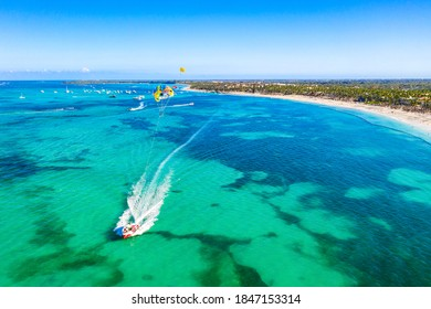 Tourists parasailing near Bavaro Beach, Punta Cana in Dominican Republic. Aerial view of tropical resort