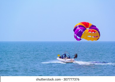 Tourists parasailing on Candolim Beach in Goa, India.