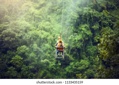 Tourists are playing zip line waterfall in Laos,Rainforest, Asia.It's an adventurous event.People are sitting on a sling.