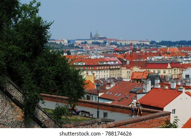 Tourists in Prague. People and aerial view of city buildings. Old architecture beautiful urban landscape. Roofs and walls of houses and barricade. City as seen from above. Friends traveling holidays.