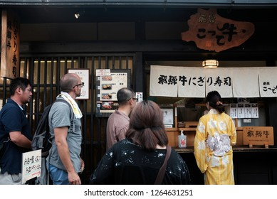 Tourists queuing up to buy famous beef sushi in old town Takayama, Japan.