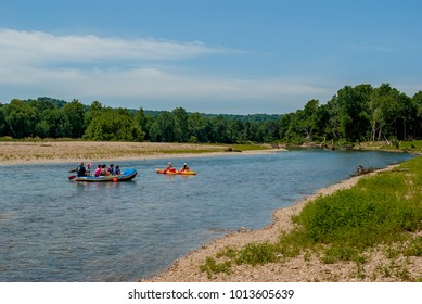 Tourists rafting down the river on a summer day with trees and blue sky