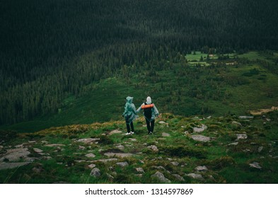Tourists in raincoats hold hands and descend from the mountain