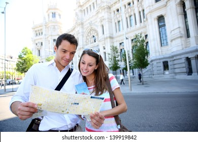 Tourists reading map in front of Palacio de Comunicaciones