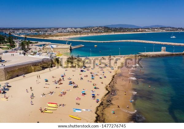 Tourists relaxing on Praia da Batata beach, Lagos, Algarve, Portugal, Europe, aerial drone wide view
