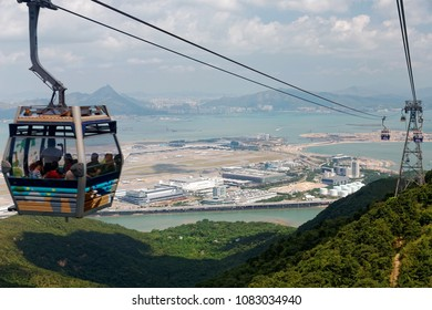 Tourists ride in a gondola of Ngong Ping Cable Car (Skyrail) gliding over the mountainside & enjoy the panoramic view of Hong Kong International Airport on Chek Lap Kok Island in Hongkong, China, Asia