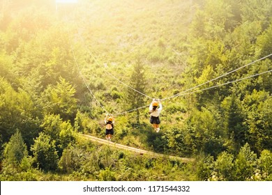 Tourists ride on the Zipline over the forest. Two women in helmets sliding on a zip line in an adventure park. Couple in helmets hanging on a rope way.