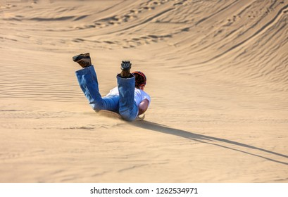 Tourists ride the sandboards from the tops of the dunes near the Huacacina oasis