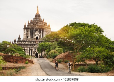 Tourists riding bicycle near ancient pagodas in Bagan, Myanmar on the sunset as it is UNESCO world heritage site