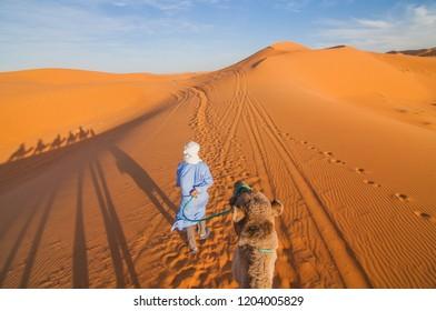 Tourists are riding camels through Sahara desert.