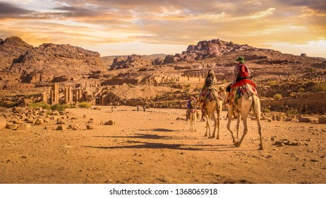 Tourists riding camels towards the Temenos Gate on the Colonnaded Street, Petra, Jordan.