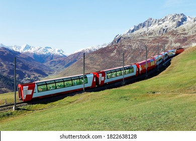 Tourists riding a Glacier Express on a brisk fall day & enjoying the view thru panoramic windows of grassy meadows on the hillside & snowy mountains under blue clear sky in Andermatt, Uri, Switzerland