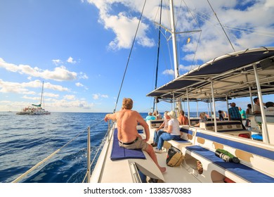 Tourists sailing around Madeira island on a catamaran looking for dolphins and whales, a popular tourist attraction, on October 11, 2015