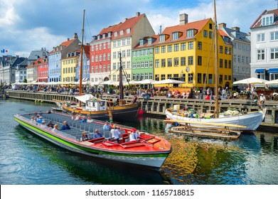 Tourists sightseeing cruising on boat by Nyhavn embankment with bars and restaurants in buildings of old architecture, Copenhagen, Denmark