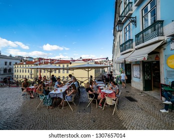 Tourists sit in a cafe over the rooftops of the old town of Lisbon, Lisbon, Portugal, Jul 2017