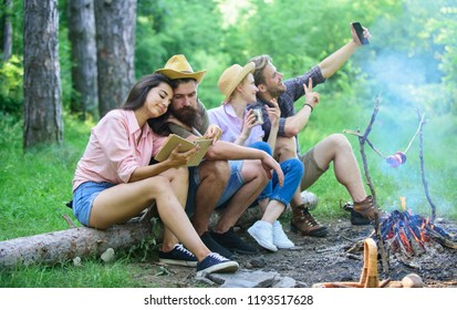 Tourists sit log near bonfire taking photo on smartphone. Friends on vacation capture moment. Friends near bonfire enjoy vacation and roasted food. Man taking photo near bonfire nature background.
