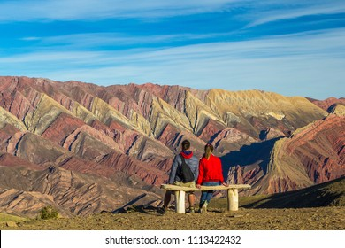 Tourists sit on a bench and look at the colored rocks at sunset Hornoсal (14 Colors Hill), Humahuaca Valley, northern Argentina.