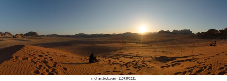 Tourists sit on a sand dune to admire sunset in Wadi Rum desert, Jordan.