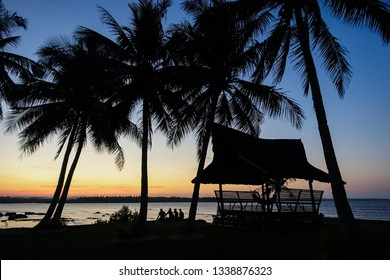 Tourists Sitting By Exotic Cottage During Beach Sunset - Siargao, Philippines