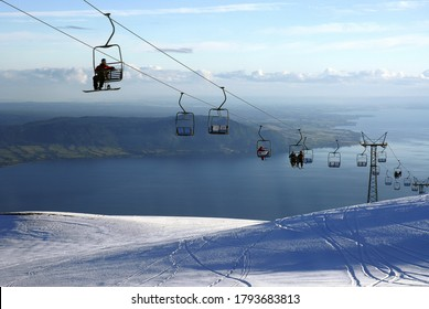 The tourists sitting on the ropeway and going up the mountain