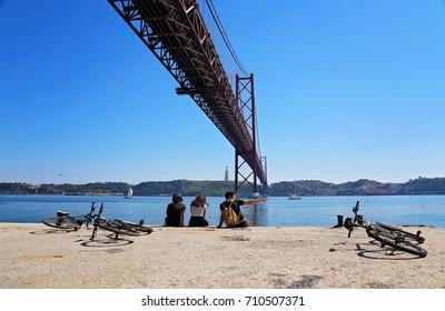 Tourists sitting under the 25 of April famous bridge in Lisbon