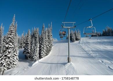 Tourists in ski lift over ski resort, Sun Peaks Resort, Sun Peaks, British Columbia, Canada