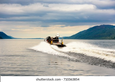 Tourists speedboating on a RIB boat (perhaps hoping to find Nessie the Loch Ness Monster) on the iconic Loch Ness, Scotland