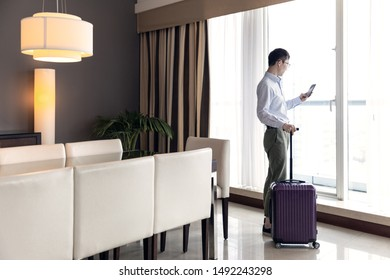 Tourists stand by the landing window of the luxury hotel
