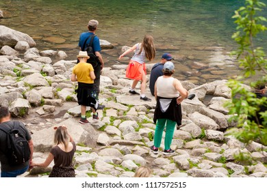 Tourists stand on stones and admire the views over 'Morskie Oko' in the mountains. Tourists at the lake, sea eye. 27 May 2018 - 'Morskie Oko', Poland.