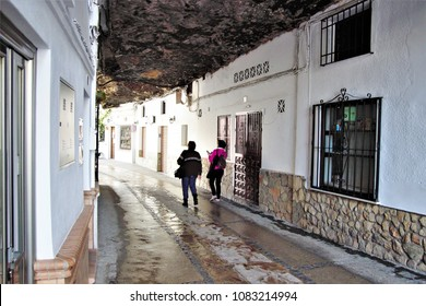 tourists strolling through Setenil, town with the houses tucked into the rock, route of the white villages in Cádiz, Andalusia, Spain,